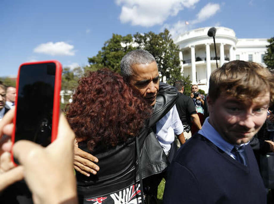 President Barack Obama hugs a guest during a surprise visit to South by South Lawn at the White House in Washington, Monday, Oct. 3, 2016. The festival is inspired by Austin's South by Southwest, with art, film and music performances and hosted by Obama. (AP Photo/Pablo Martinez Monsivais)