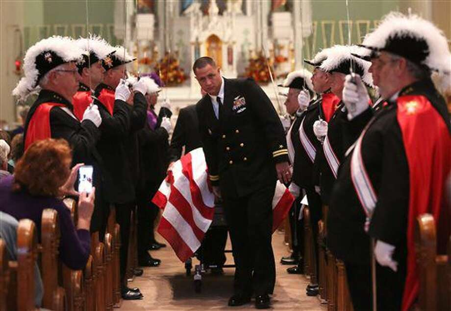 Lt. Brian Lewis escorts the casket before the Mass of remembrance for Chaplain Aloysius Schmitt on Wednesday, Oct. 5, 2016, at St. Luke's Church in St. Lucas, Iowa. Schmitt, a St. Lucas, native, died on Dec. 7, 1941, when the Japanese attacked Pearl Harbor. After nearly 75 years, his remains have been identified. (V/Telegraph Herald via AP)