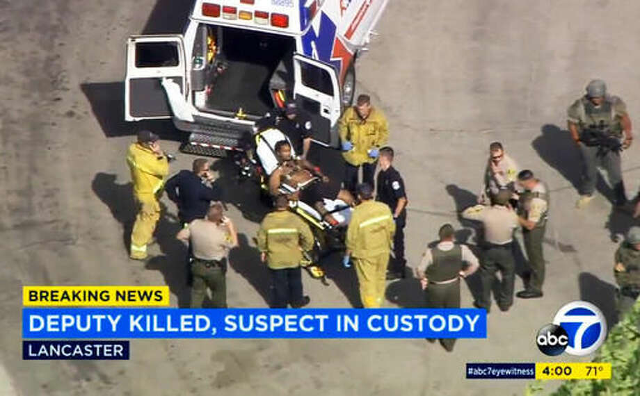 In this still frame from video provided by KABC-TV, Los Angeles County Sheriff's deputies and firefighters wheel a wounded man, a suspect in the shooting death of a deputy, to an ambulance in Lancaster, Calif., Wednesday, Oct. 5, 2016. Sgt. Steve Owen was shot and killed while answering a burglary report, and the suspected gunman was arrested after commandeering his patrol car, ramming a second police vehicle, then hiding in a home as two teenagers cowered, authorities said. (KABC-TV via AP) MANDATORY CREDIT; TV OUT; NO SALES