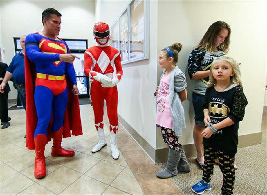 Zowie Sanders, right, stands near John Suber, left, of Greenville, S.C. dressed as Superman, with her sister Lindsey Sanders, middle, and their mother Brooke Starks, right, during a wake service for Jacob Hall, at Oakdale Baptist Church, Tuesday, Oct. 4, 2016 in Townville, S.C. Townspeople and classmates filled a church Tuesday evening to say goodbye to Jacob Hall, a 6-year-old boy who died in a school shooting, filing past a casket adorned with large photos, balloons and a life-size figure of one of his favorite superheroes, Batman.(Ken Ruinard/The Independent-Mail via AP, Pool)