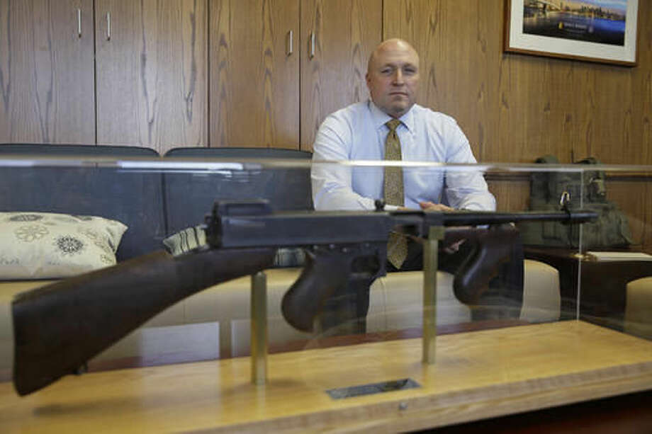 In this photo taken Tuesday, Sept. 27, 2016, FBI Special Agent Jack Bennett poses behind an encased Thompson Submachine gun in his office in San Francisco. The FBI's new leader in San Francisco is a former drug investigator who developed expertise in technology that put him at the center of the government's effort to unlock an iPhone used by one of the San Bernardino shooters. Bennett now has oversight responsibilities for Silicon Valley. (AP Photo/Eric Risberg)
