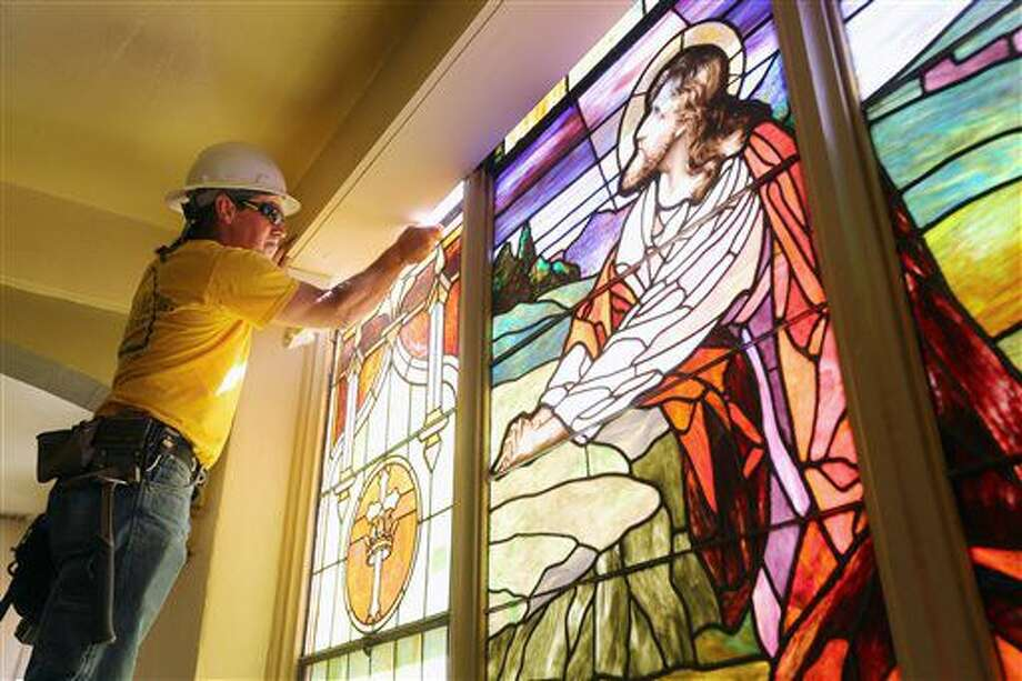 ADVANCE FOR SUNDAY OCT. 2 - In this Monday Sept. 19, 2016 photo, Mike McMullin, with with Bovard Studio Inc., of Fairfield, works on removing a stain glass window from St. Mary's and Patrick's Catholic Church, in West Burlington, Iowa. The windows which were being removed as part of the church's remodeling project, will be reinstalled at a later date. Work began in mid-August, and when it's done, the church will have a larger gathering space at the entrance. The entrance itself is being moved to the center of the building, and a new drop-off lane will allow parishioners to drop off elderly residents at the entrance. (John Lovretta/The Hawk Eye via AP)