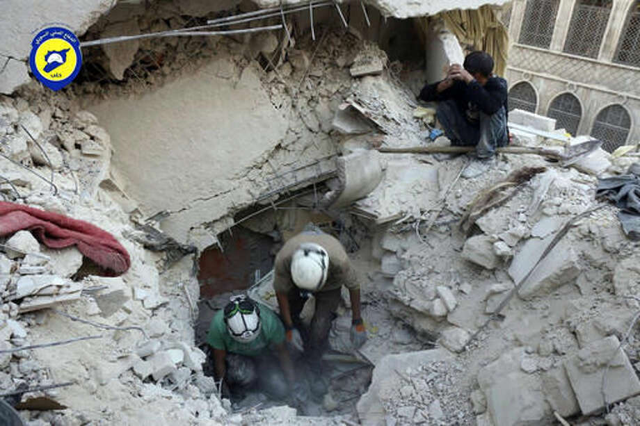This Tuesday, Oct. 4, 2016 photo, provided by the Syrian Civil Defense group known as the White Helmets, shows Civil Defense workers from the White Helmets digging in the rubles to remove bodies and look for survivors, after airstrikes hit the Bustan al-Basha neighborhood in Aleppo, Syria. The U.N. on Wednesday released stark satellite images showing the most recent destruction of Syria's embattled northern city of Aleppo, pounded by Syrian and Russian airstrikes since the collapse of a U.S.-Russia brokered cease-fire two weeks ago. (Syrian Civil Defense White Helmets via AP)