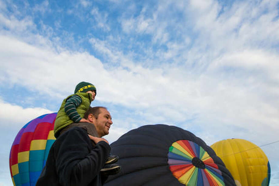 In this Friday, Sept. 23, 2016 photo, Jarrod Schulte, of Kennewick, Wash., carries his son Greyson on his shoulders while viewing the balloons during the first day of the Great Prosser Balloon Rally in Prosser, Wash. McKenna Secrist's 16th birthday in July came with a hot air balloon pilot's license instead of a driver's license. Secrist joined more than a dozen hot air balloon pilots at the Great Prosser Balloon Rally, where they fired up their colorful conveyances at the Prosser Airport. (Shawn Gust/Yakima Herald-Republic via AP)