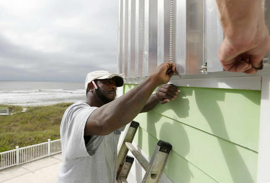 Dimitri Pinckney installs hurricane shutters in advance of Hurricane Matthew on the Isle of Palms, S.C., Wednesday, Oct. 5, 2016. Hurricane Matthew is expected to affect the South Carolina coast by the weekend. Gov. Nikki Haley announced Tuesday that, unless the track of the storm changes, the state will issue an evacuation order Wednesday to help get 1 million people inland from the coast. (AP Photo/Mic Smith)