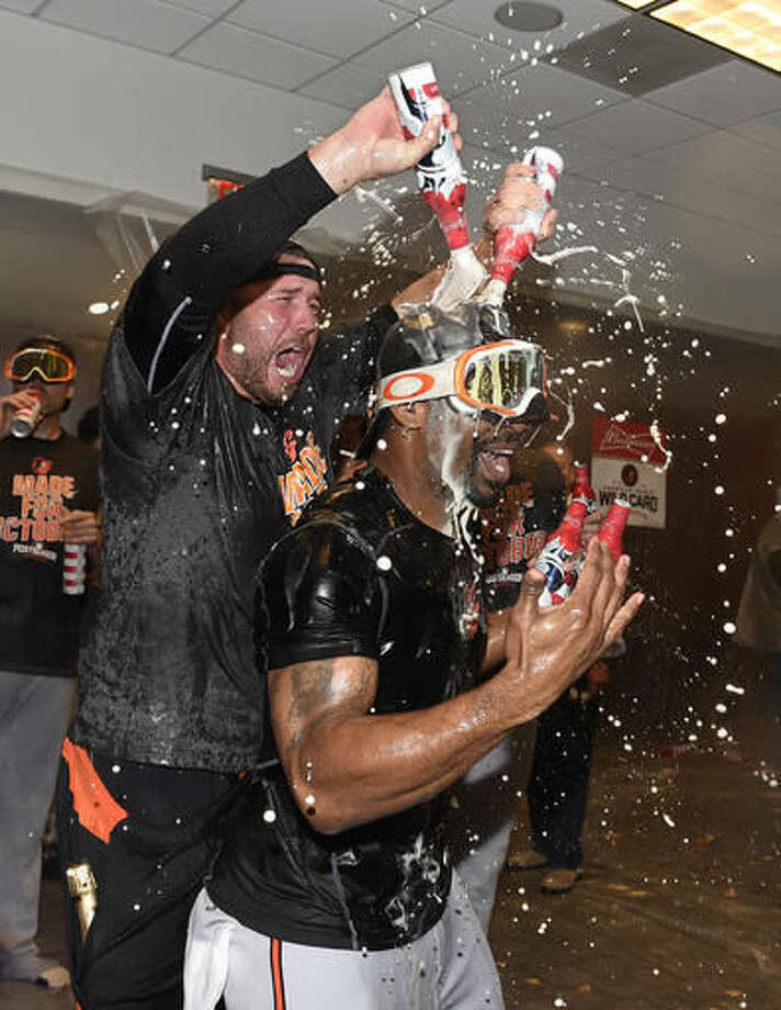 Baltimore Orioles pitcher Tommy Hunter pours beer over Michael Bourn in the visitors' clubhouse after the Orioles defeated the New York Yankees 5-2 in a baseball game to go to the playoffs , Sunday, Oct. 2, 2016, in New York. (AP Photo/Kathy Kmonicek)