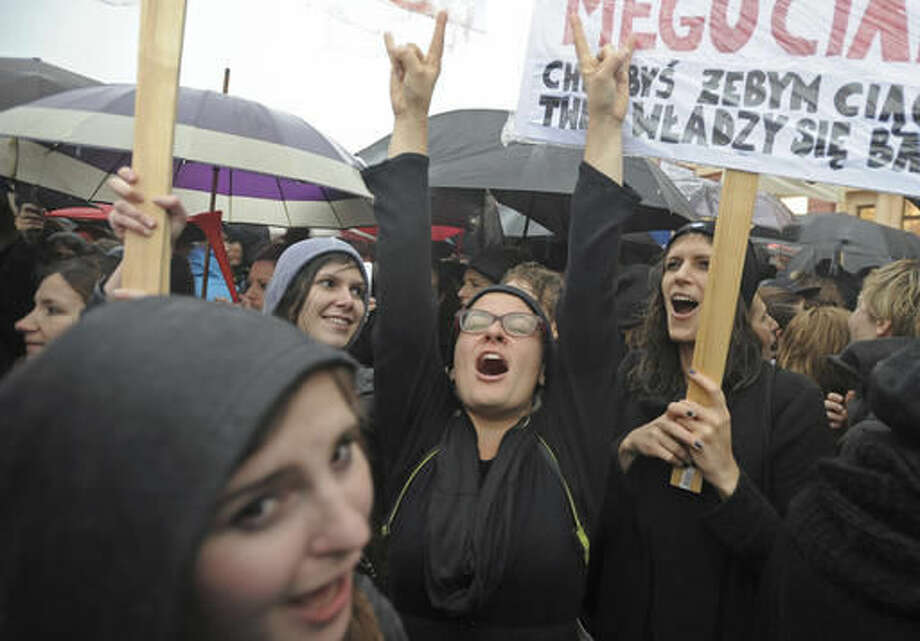 "Women shout slogans during a demonstration at the Castle Square during a nationwide ""Black Monday"" strike to protest a legislative proposal for a total ban on abortion, in Warsaw, Poland, Monday, Oct. 3, 2016. Massive protests were held in the rain in the streets of Warsaw, Gdansk, Wroclaw and elsewhere across the largely Catholic nation led by a conservative government. (AP Photo/Alik Keplicz)"
