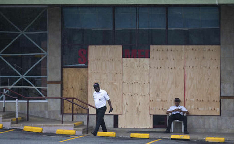 A security guardzs sits in front of a store that had its windows covered with plywood in preparation for the arrival of Hurricane Matthew in Kingston, Jamaica, Monday, Oct. 3, 2016. Major Hurricane Matthew is slowly churning northward across the Caribbean and meteorologists say the powerful storm is expected to approach Jamaica and southwest Haiti by Monday night. (AP Photo/Eduardo Verdugo)