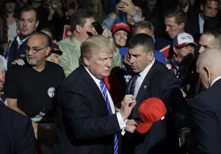 Republican presidential candidate Donald Trump signs a hat after a rally, Friday, Sept. 30, 2016, in Novi, Mich. (AP Photo/John Locher)