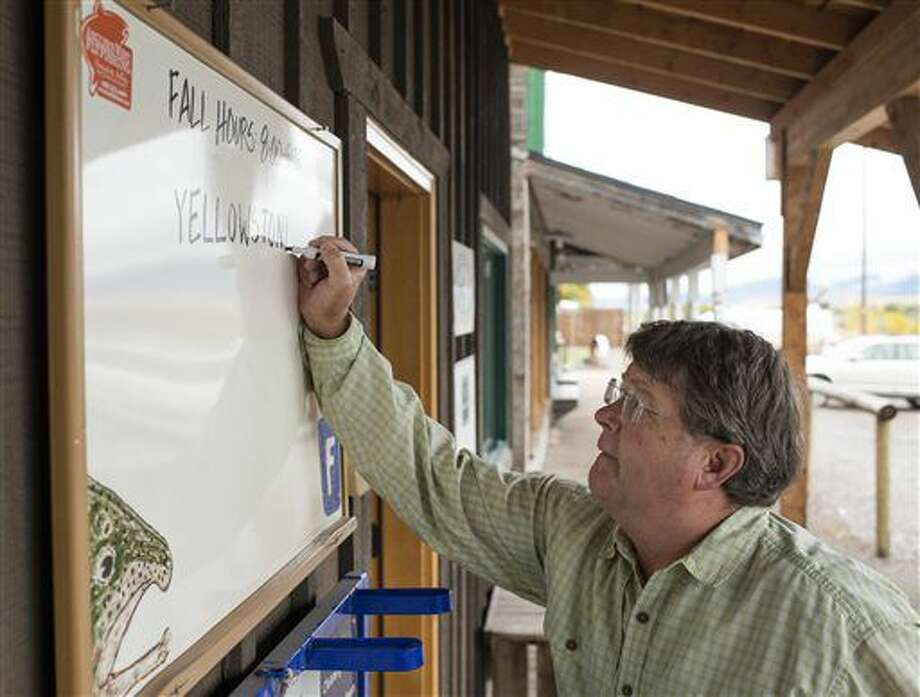 In this Sept. 23, 2016 photo, Rick Wollum, retail sales manager at Angler's West Fly Fishing Outfitters, rewrites the board outside the fly shop to reflect the open status of the Yellowstone River, in Bozeman, Mont. Previously the whiteboard was used to inform anglers of which sections of the river were closed to fishing. (Rachel Leathe/Bozeman Daily Chronicle via AP)