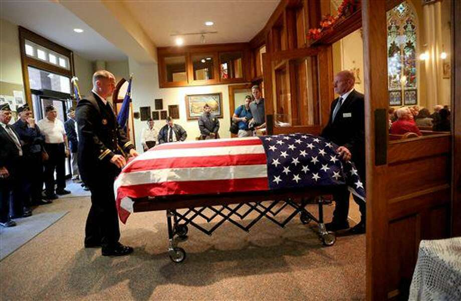 Lt. Brian Lewis, left, and Pat Leonard prepare to fold the flag before a Mass of remembrance for Chaplain Aloysius Schmitt on Wednesday, Oct. 5, 2016, at St. Luke's Church in St. Lucas, Iowa. Schmitt, a St. Lucas, native, died on Dec. 7, 1941, when the Japanese attacked Pearl Harbor. After nearly 75 years, his remains have been identified. (Jessica Reilly/Telegraph Herald via AP)