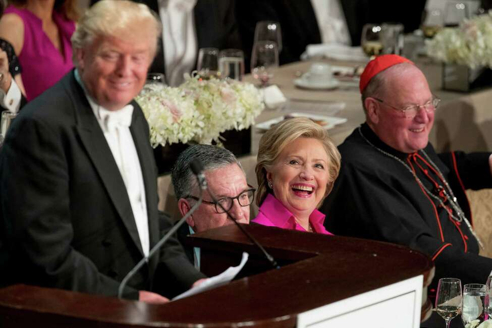 Republican presidential candidate Donald Trump, left, accompanied by Democratic presidential candidate Hillary Clinton, second from right, and Cardinal Timothy Dolan, Archbishop of New York, right, speaks at the 71st annual Alfred E. Smith Memorial Foundation Dinner, a charity gala organized by the Archdiocese of New York, Thursday, Oct. 20, 2016, at the Waldorf Astoria hotel in New York. (AP Photo/Andrew Harnik) ORG XMIT: NYAH117