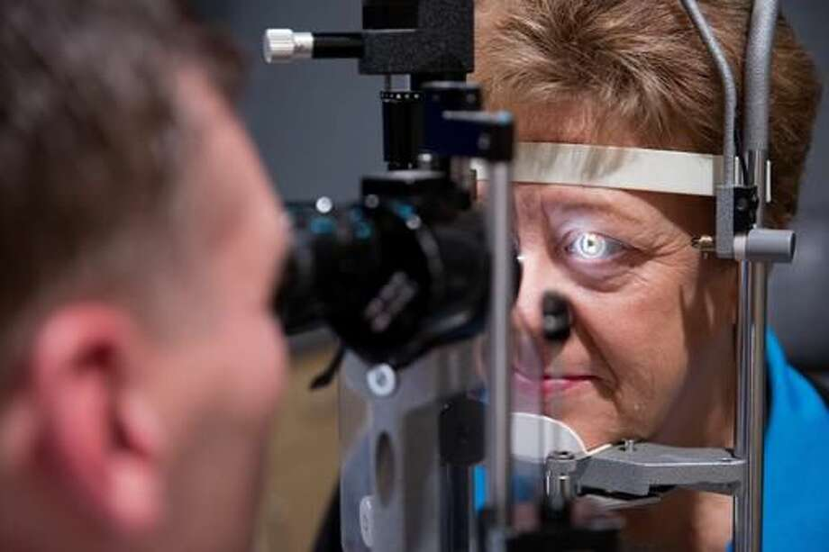 In this Friday, Sept. 16, 2016 photo, Dr. Lance Kugler examines Cheryl Henry's left eye during a follow-up visit at Kugler Vision in Omaha, Neb. (Rebecca Gratz /Omaha World-Herald via AP)