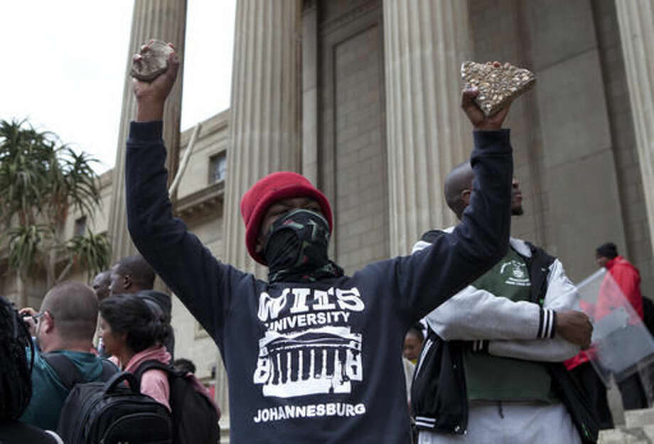 A student gestures, on a campus of the University of the Witwatersrand in Johannesburg Tuesday, Oct. 4, 2016, during clashes with police and private security officers. Police fired rubber bullets and set off stun grenades to disperse the protesters after the university announced it was re-opening despite sometimes violent demonstrations for free education. (AP Photo/Wikus de Wet)