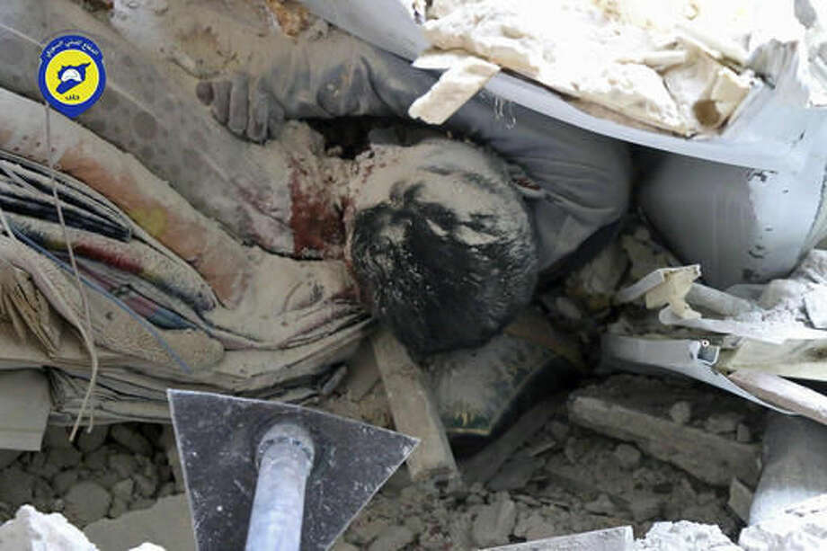 This Tuesday, Oct. 4, 2016, photo provided by the Syrian Civil Defense group known as the White Helmets, shows a body under the ruble of a destroyed building following an airstrike, at Bustan al-Basha neighborhood in Aleppo, Syria. The U.N. on Wednesday released stark satellite images showing the most recent destruction of Syria's embattled northern city of Aleppo, pounded by Syrian and Russian airstrikes since the collapse of a U.S.-Russia brokered cease-fire two weeks ago. (Syrian Civil Defense White Helmets via AP)