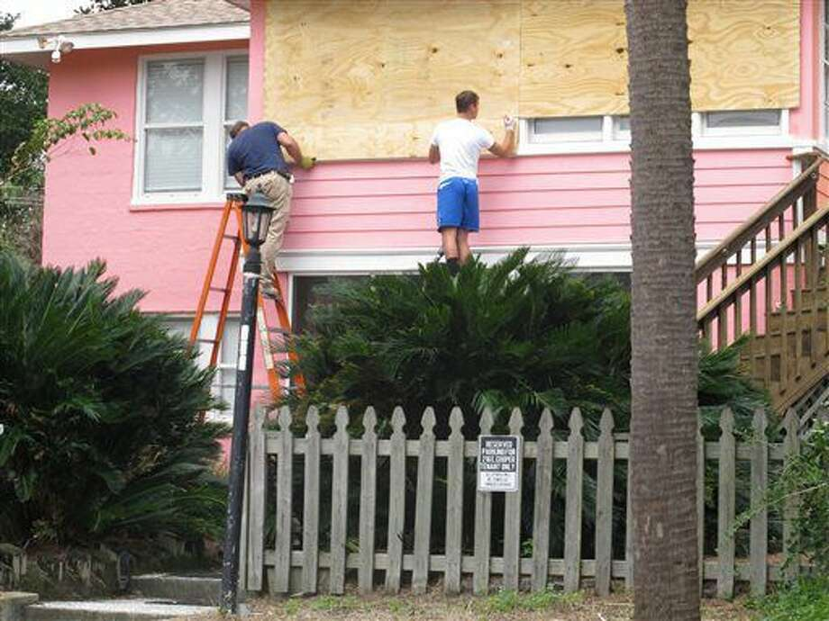 Workers hammer plywood over the windows of a home in Folly Beach. S.C., on Wednesday, Oct. 5, 2016. The winds and rains of Hurricane Matthew are expected to affect the South Carolina coast by late in the week. (AP Photo/Bruce Smith)