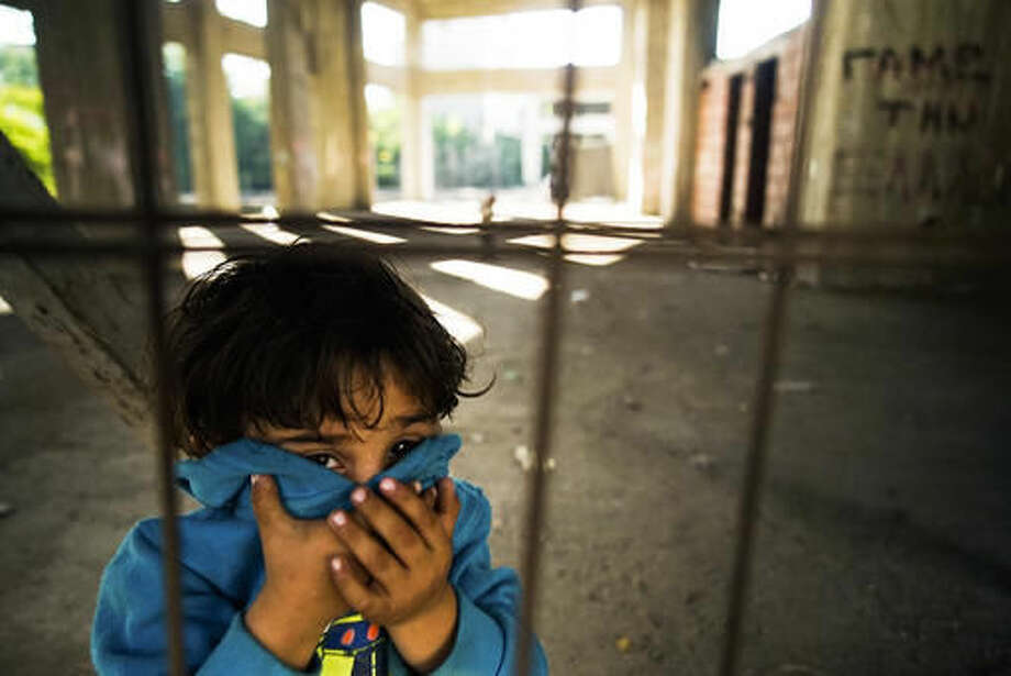 In this Monday, Oct. 3, 2016 photo, a child looks on in an unfinished building site, near the train station at Thessaloniki, Greece, which migrants and other refugees use as a temporary shelter before their attempt to illicitly cross the Greek-Macedonian border. Despite Macedonia's construction of a fence, dozens of people try to sneak across the border every day, hoping to make their way to Europe's prosperous heartland. Police have been detaining about 50 people daily, and arresting members of smuggling gangs that promise to get migrants to their destinations. About 60,000 refugees and other migrants are trapped in financially-struggling Greece(AP Photo/Mstyslav Chernov)