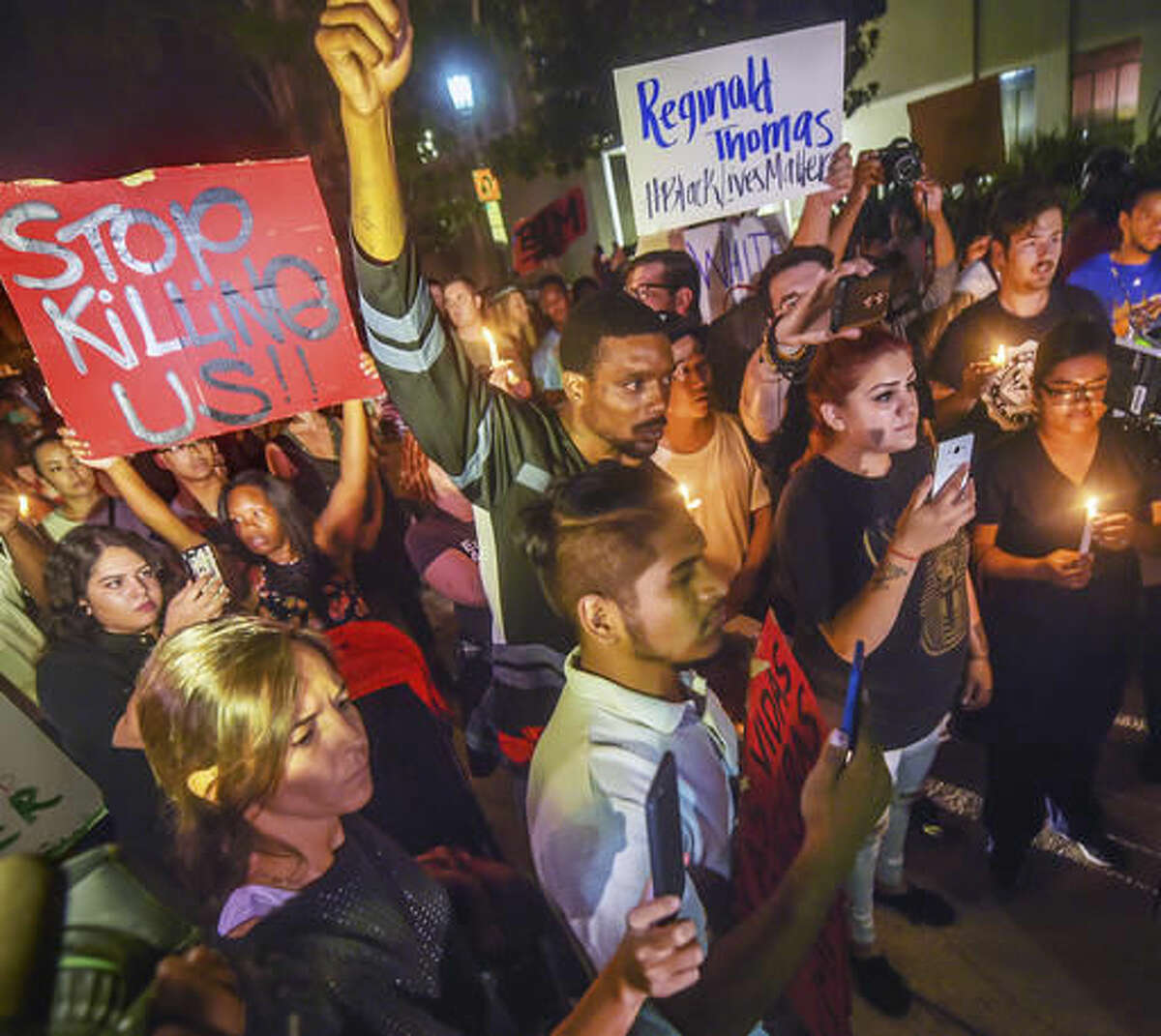 Protesters walk on Garfield Avenue adjacent to the Pasadena City Hall in a candlelight vigil for Reginald Thomas who died earlier in Pasadena Police custody in Pasadena, Calif., on Friday, Sept. 30, 2016. (Walt Mancini/The Pasadena Star-News via AP)