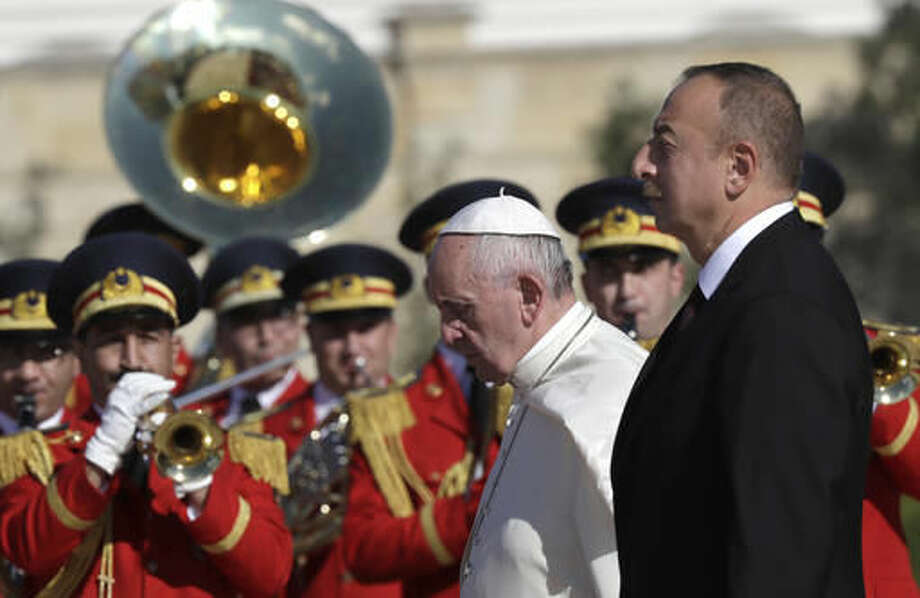 Pope Francis and Azerbaijan's President Ilham Aliyev, foreground right, review of the honor guard on the occasion of their meeting at the presidential palace, in Baku, Azerbaijan, Sunday, Oct. 2, 2016. Francis traveled to Azerbaijan on Sunday for a 10-hour visit aimed at encouraging the country's inter-religious harmony while likely overlooking criticism of a referendum that extends the president's term and powers. (AP Photo/Alessandra Tarantino)
