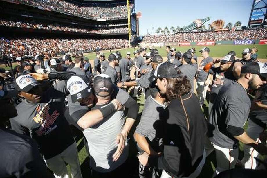 San Francisco Giants players celebrate on the field after clinching a second place wild card spot following their 7-1 win over the Los Angeles Dodgers in a baseball game in San Francisco, Sunday, Oct. 2, 2016. (AP Photo/Tony Avelar)