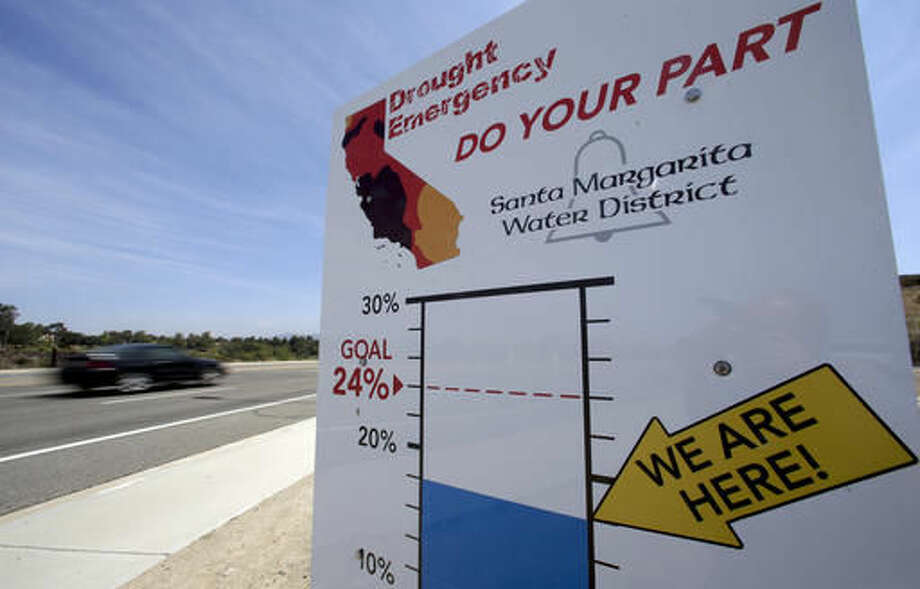 FILE - In this July 2, 2015, file photo, cars by a sign encouraging residents to save water in Rancho Santa Margarita, Calif., drive. State regulators said Wednesday, Oct. 5, 2016, water conservation continues to slip in drought-stricken California after officials lifted mandatory cutbacks. (AP Photo/Chris Carlson, File)