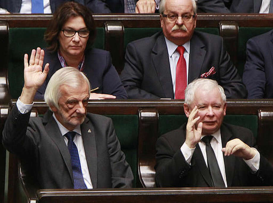 Jaroslaw Kaczynski, right, head of the ruling Law and Justice party, votes in a parliament to reject a proposal to restrict the abortion law in Warsaw, Poland, Thursday, Oct. 6, 2016. He was one of the lawmakers who objected a proposal by an anti-abortion group that would have imposed a total ban on abortion. (AP Photo/Czarek Sokolowski)