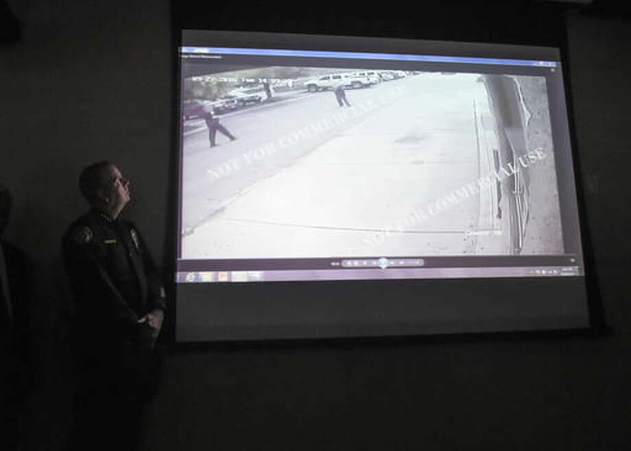 Escondido Police Chief Craig Carter, left, watches a video of the shooting scene at a news conference on Friday Sept. 30, 2016, in El Cajon, Calif, held to address the killing of Alfred Olango, a Ugandan refugee shot by an El Cajon police officer on Tuesday. The El Cajon police department released video footage of the shooting at the news conference. (AP Photo/Denis Poroy)