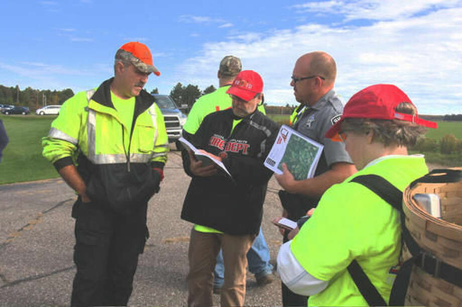 Langlade County Sheriff's Deputy D.J. Eldridge gathers with volunteers Sunday, Oct. 2, 2016, northeast of Antigo, Wisc., where a boy had become lost in a corn field late Saturday. The youngster was found safe and unharmed Sunday after a huge turnout of volunteers, fire departments and law enforcement in the area. (Fred Berner/Antigo Daily Journal via AP)