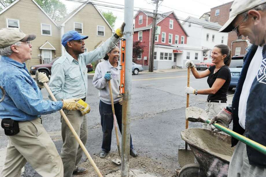 Bob Stephan, Ted Foster, Georgette Scott, Katherine Tenney and Rudy Atroziencik volunteer with Community Bridgebuilders, a coalition of faith based groups that partner with Habitat for Humanity, and work on a building on West Main Street in Stamford, Conn. on Friday May 14, 2010. Photo: Kathleen O'Rourke / Stamford Advocate