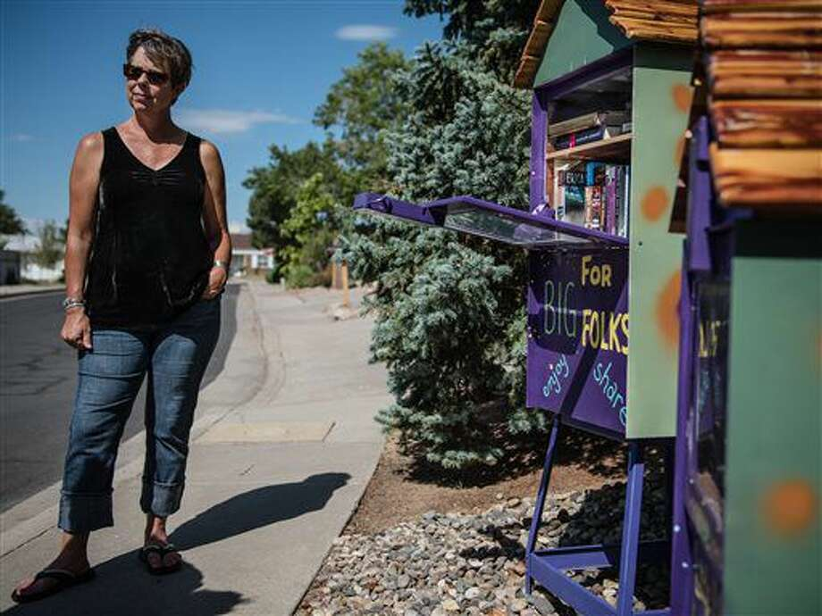 In this Sept. 22, 2016 photo, Diane Metzler, a neighbor of Bob Shipley, and a regular user of the Little Free Library, stands in front of repurposed newspaper dispensers in Albuquerque, N.M. Shipley got the idea to use old newspaper vending machines from the Albuquerque Journal and turn them into Little Libraries for his Northeast heights neighborhood. (Roberto E. Rosales/The Albuquerque Journal via AP)