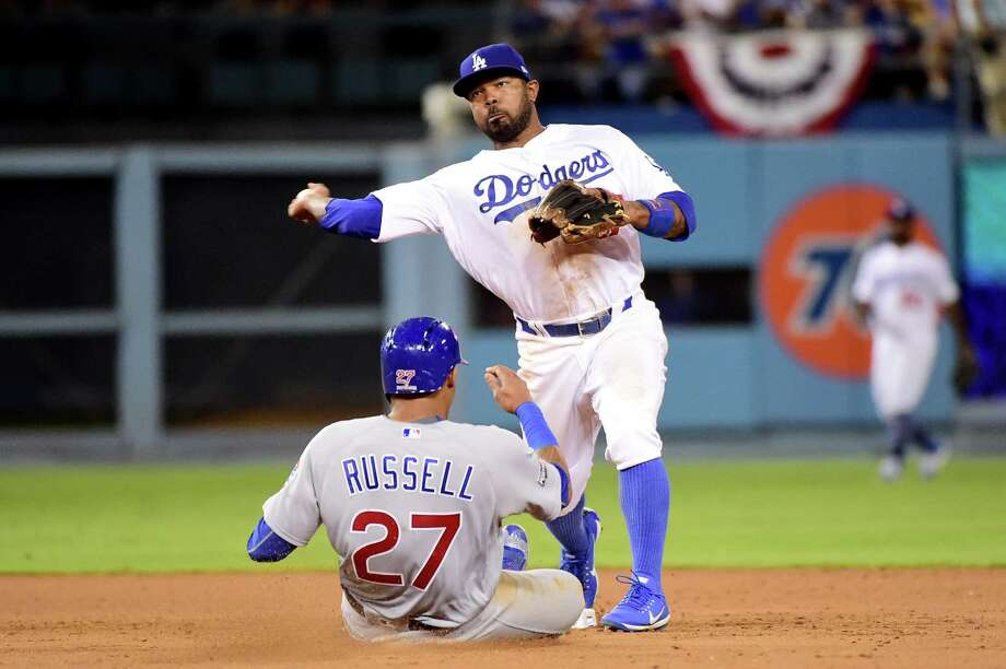 LOS ANGELES, CA - OCTOBER 20:  Howie Kendrick #47 of the Los Angeles Dodgers turns a double play as Addison Russell #27 of the Chicago Cubs is out at second base in the ninth inning in game five of the National League Division Series at Dodger Stadium on October 20, 2016 in Los Angeles, California. Photo: Harry How, Getty Images / 2016 Getty Images