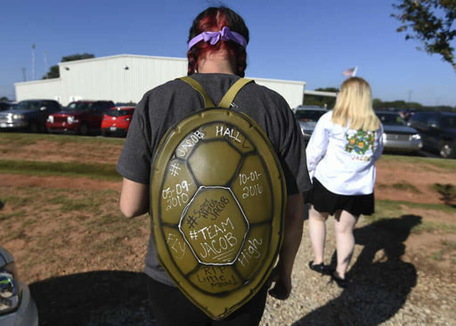 Kortnie Lanclos, of Liberty, S.C., wears a Teenage Mutant Ninja Turtles shell before a superhero-themed funeral service for Jacob Hall at Oakdale Baptist Church on Wednesday, Oct. 5, 2016, in Townville, S.C. Jacob's family has encouraged people to celebrate his life by dressing as the superheroes he loved. A 14-year-old boy killed his own father, then drove to Townville Elementary and fired on two children and a teacher as recess began. Jacob died Saturday. (AP Photo/Rainier Ehrhardt)