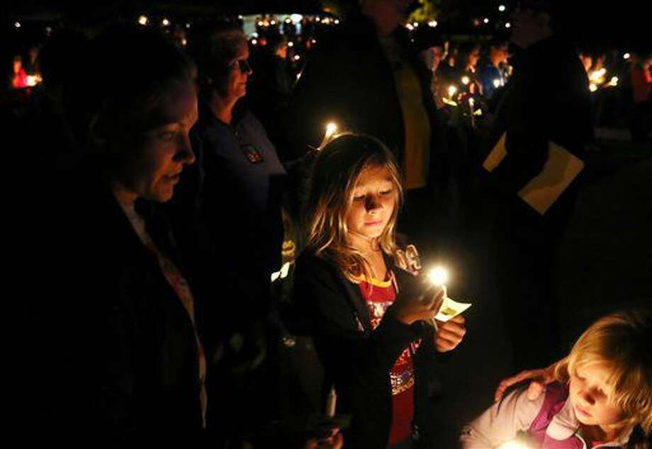 Olivia Stephens, center, 9, of Roseburg, Ore., middle, with her mother Rachel Stephens, left, and sister Emma Stephens, 4, participates in a candlelight vigil in remembrance of the mass shooting at Umpqua Community College one year ago, in Roseburg, Ore., Saturday Oct. 1, 2016 (Michael Sullivan/The News-Review via AP)