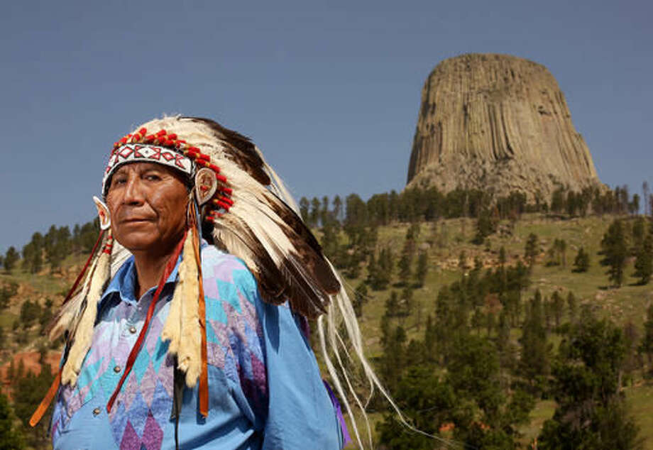 FILE - This Thursday, July 9, 2015 file photo shows Chief Arvol Looking Horse, spiritual leader of the Great Sioux Nation, posing for a portrait in front of Devils Tower National Monument in Devils Tower, Wyo. As the nation's first national monument approaches its 110th anniversary in 2016, Arvol Looking Horse has petitioned to change the name of the geologic feature to Bear Lodge and the name of the monument to Bear Lodge National Monument. Opponents of the idea say changing the name would cause confusion and hurt tourism. (Dan Cepeda/The Casper Star-Tribune via AP, File)
