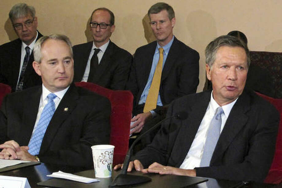 FILE - In this June 26, 2015, file photo, Ohio Gov. John Kasich, front right, and Ohio Senate President Keith Faber, front left, both Republicans, discuss the state budget with reporters, as other officials watch at the Statehouse in Columbus, Ohio. Ohio Senate President Keith Faber is a lead sponsor of a bill passed by the state Senate on Wednesday, Sept. 28, 2016, that would create a review process for at least 25 state agencies under the governor's authority, allowing lawmakers to more easily eliminate agencies. (AP Photo/Kantele Franko, File)