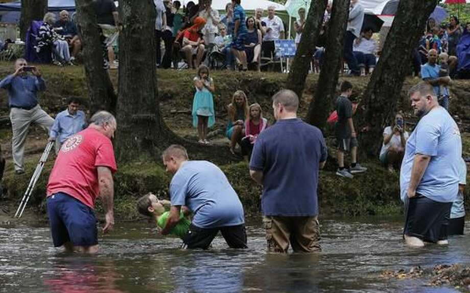 Jamie Spinks baptizes his son, Grayson, 8, in the Chattahoochee River, Sunday, Sept. 18, 2016, near Demorest, Ga. Children from age 7 and adults into their 70s are baptized by pastors or family. (AP Photo/Mike Stewart)
