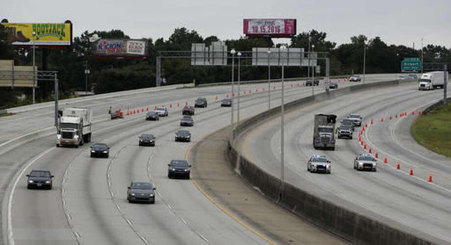 South Carolina state troopers, right, lead the first wave of cars evacuating on the reverse lane of Interstate 26 Wednesday, afternoon, Oct. 5, 2016, as traffic headed towards Columbia, S.C., near the Remount Road overpass in North Charleston, S.C., in advance of Hurricane Matthew. (AP Photo/Mic Smith)
