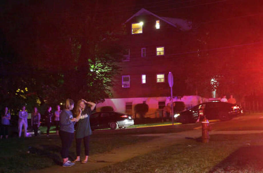 In this Tuesday, Oct. 4, 2016 photo provided by The Miami Student, a university newspaper, Miami University students gather across the street from a police investigation in Oxford, Ohio, where two Miami University students were shot and wounded near campus. The male students were shot and wounded while trying to buy a car that was posted for sale on Craigslist, police said. The students were shot during an apparent robbery Tuesday night at a house near campus. (A.J. Newberry/The Miami Student via AP)