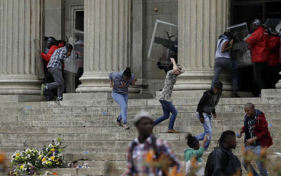 Protesting students throw stones against security at the University of the Witwatersrand in Johannesburg, South Africa, Tuesday, Oct. 4, 2016. South African police have fired rubber bullets and set off stun grenades to disperse student protesters on a university campus in Johannesburg. The clash occurred Tuesday at the University of the Witwatersrand, which had announced it was re-opening after closing because of sometimes violent demonstrations for free education. (AP Photo/Themba Hadebe)