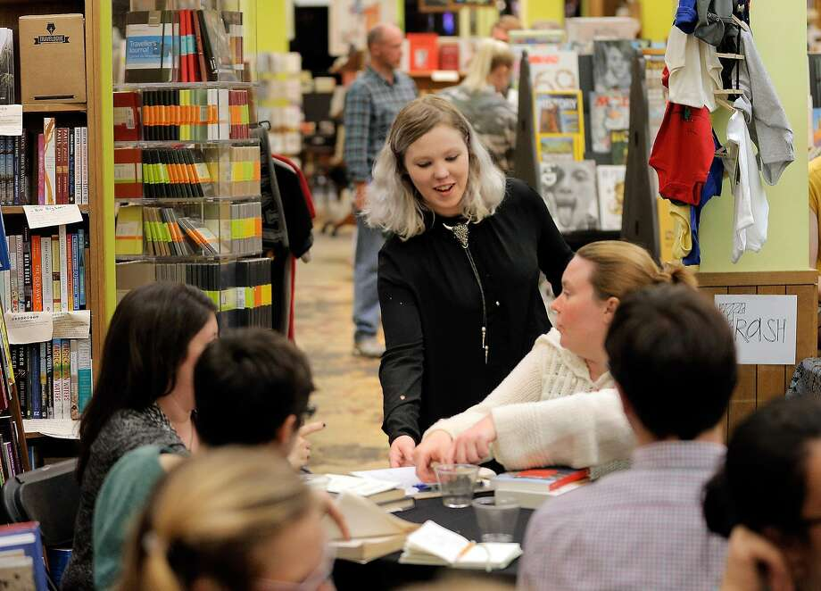 Coley Gold, events manager for Booksmith, check on guests during a book swap. Photo: Carlos Avila Gonzalez, The Chronicle