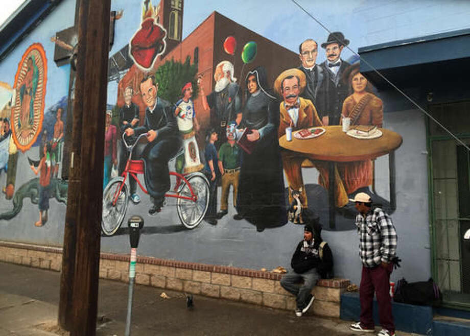 FILE - In this Jan. 5, 2016, file photo, residents stand near a mural with Chicano historical figures in the Segundo Barrio of El Paso, Texas. El Paso's Chihuahuita and El Segundo Barrio Neighborhoods made The National Trust for Historic Preservation's 2016 list of America's 11 Most Endangered Historic Places, an annual list that spotlights important examples of the nation's architectural and cultural heritage that are at risk of destruction or irreparable damage. (AP Photo/Russell Contreras, File)