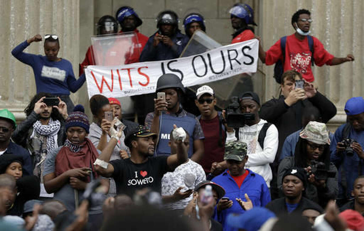A protester, centre left, addresses fellow students outside the great hall at the University of the Witwatersrand in Johannesburg, South Africa, Tuesday, Oct. 4, 2016. South African police have fired rubber bullets and set off stun grenades to disperse student protesters on a university campus in Johannesburg. The clash occurred Tuesday at the University of the Witwatersrand, which had announced it was re-opening after closing because of sometimes violent demonstrations for free education. (AP Photo/Themba Hadebe)