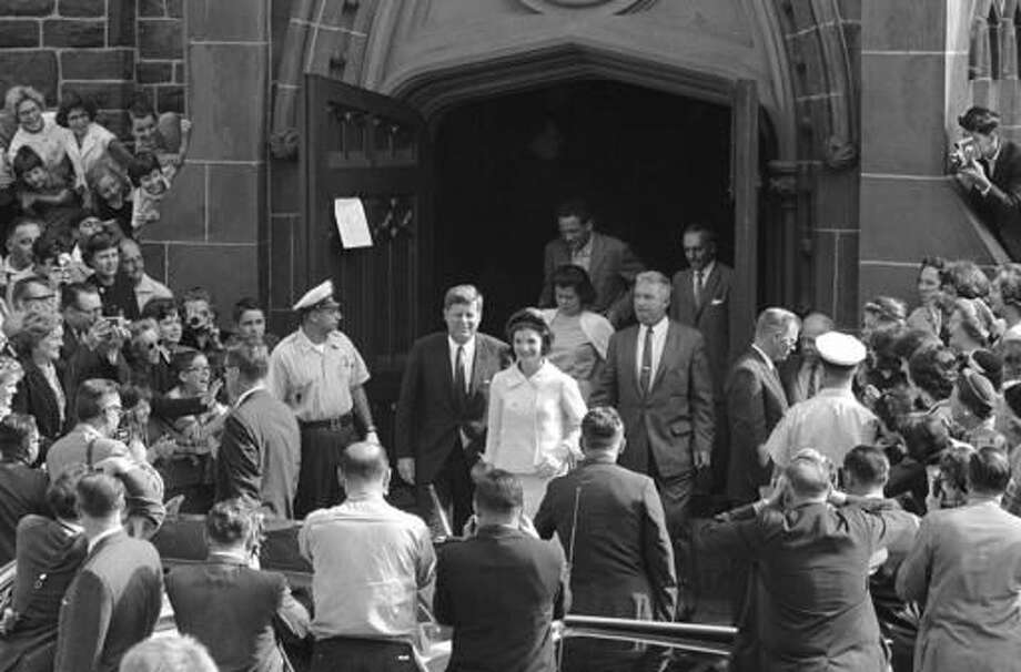 FILE - In this Oct. 1, 1961 file photo, President John F. Kennedy and first lady Jacqueline Kennedy, accompanied by Charles Bartlett and his wife, leave St. Mary's Church in Newport, R.I., after Mass. The church where the couple was married is being restored in 2016 to the appearance it had on their y Sept. 12, 1953, wedding day. (AP Photo/File)