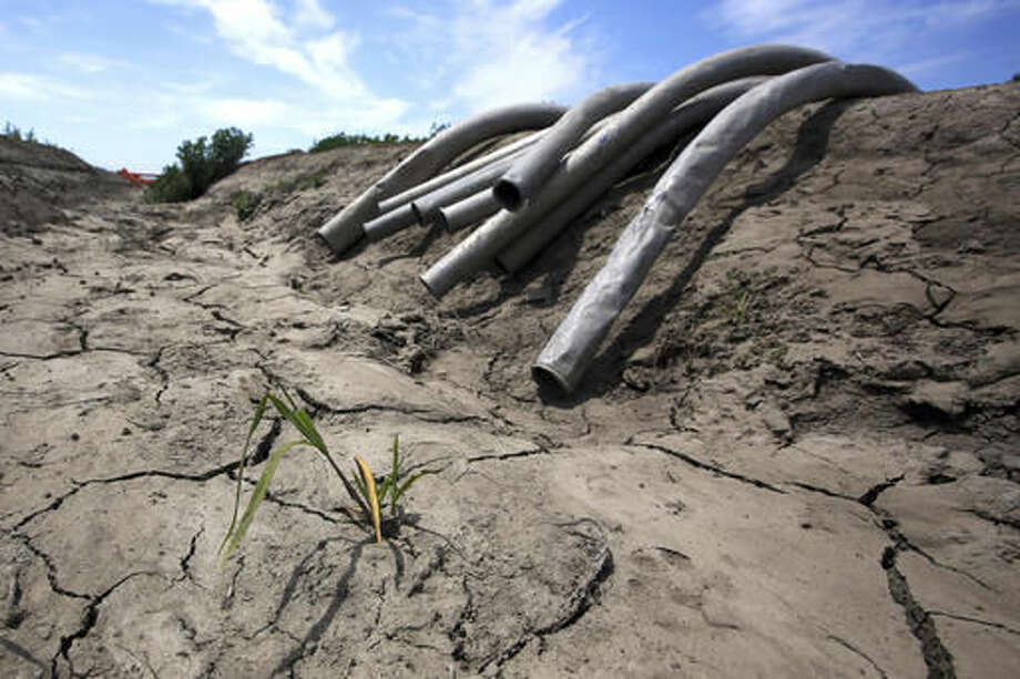 FILE - In this May 18, 2015 file photo, irrigation pipes sit along a dry irrigation canal on a field near Stockton, Calif. State regulators said Wednesday, Oct. 5, 2016, water conservation continues to slip in drought-stricken California after officials lifted mandatory cutbacks. (AP Photo/Rich Pedroncelli, File)