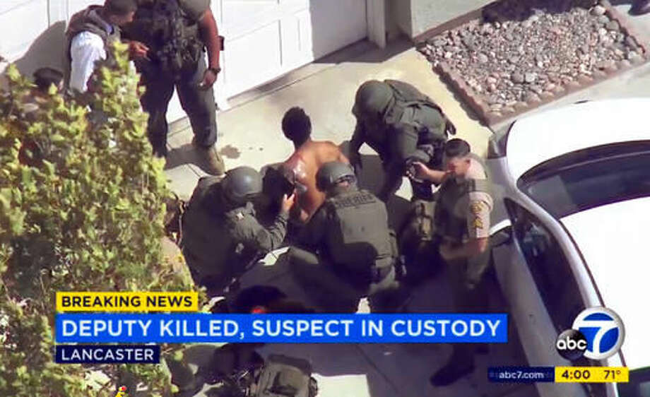 In this still frame from video provided by KABC-TV, Los Angeles County Sheriff's deputies take into custody a wounded man, who is a suspect in the shooting death of a deputy, in Lancaster, Calif., Wednesday, Oct. 5, 2016. Sgt. Steve Owen was shot and killed while answering a burglary report, and the suspected gunman was arrested after commandeering his patrol car, ramming a second police vehicle, then hiding in a home as two teenagers cowered, authorities said. (KABC-TV via AP) MANDATORY CREDIT; TV OUT; NO SALES