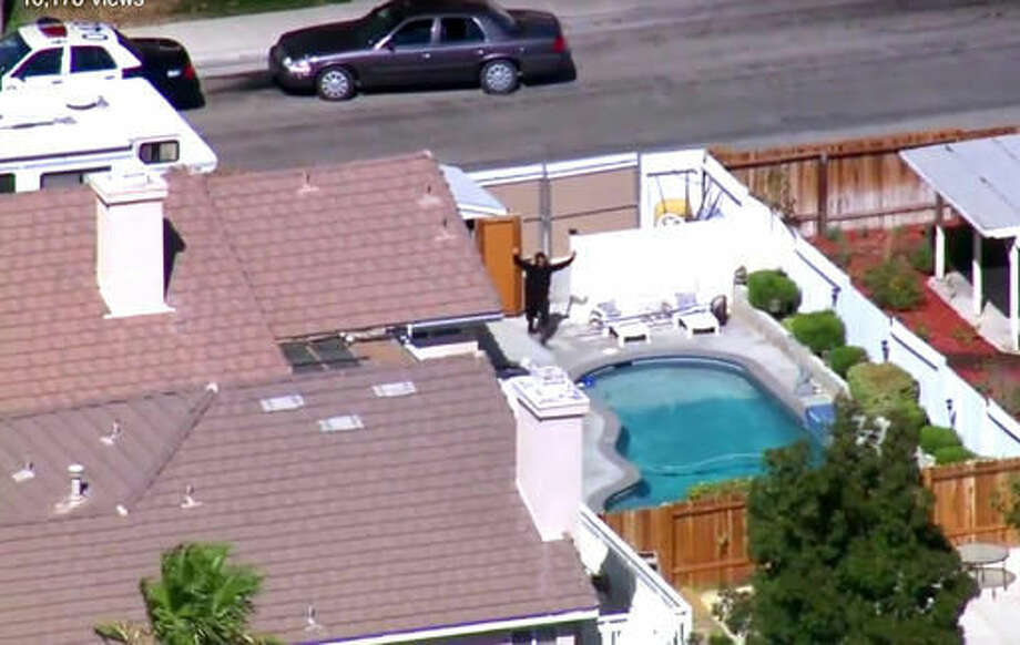 This still frame from video provided by KTTV-TV shows a man with his hands up in the backyard of a home, after first looking over the gate behind him and seeing law enforcement vehicles, as authorities search for a gunman who shot and killed Los Angeles County Sheriff Sgt. Steve Owen, in Lancaster, Calif., Wednesday, Oct. 5, 2016. The sergeant was shot and killed while answering a burglary report and the suspected gunman was arrested after ramming the sergeant's stolen patrol car into another patrol car and fleeing to a nearby home, authorities said. (KTTV-TV via AP) MANDATORY CREDIT; TV OUT; NO SALES