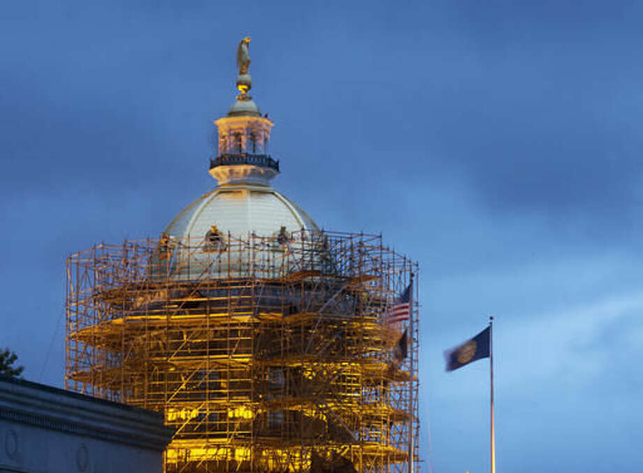 This Sept. 28, 2016 photo shows the newly re-gilded gold dome at New Hampshire's statehouse in Concord, N.H. Workers have begun to dismantle the scaffolding around the dome on the Civil War-era statehouse. The makeover comes as the state launches a three-year-old bicentennial celebration of the State House and its grounds. (AP Photo/Jim Cole)