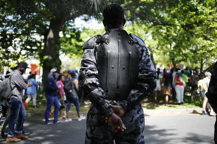 A security guard patrols as students from the University of Cape Town protest in Cape Town, South Africa, Tuesday, Oct. 4, 2016, demanding free university education. President Jacob Zuma has said the recent protests at some South African universities have caused about $44 million in property damage and threaten to sabotage the country's system of higher education. (AP Photo/Schalk van Zuydam)