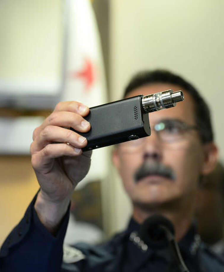 El Cajon Police Department Capt. Jeffery Davis holds up a vape device similar to the one that they claim that Alfred Olango was holding when he was shot during at a news conference held on Friday Sept. 30, 2016, in El Cajon, Calif. The El Cajon police department released video footage of the shooting at the news conference. (AP Photo/Denis Poroy)