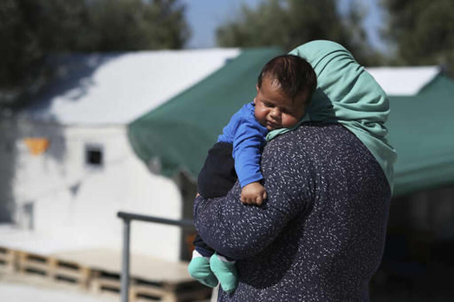 A woman carries her baby at the Kara Tepe camp for refugees and other migrants in Lesbos island, Greece, on Thursday, Oct. 6, 2016. More than a million migrants and refugees crossed through Greece and on to other EU countries since the start of 2016, while over 60,000 have been stranded in the country since the EU-Turkey deal took effect and the Balkan transit route north was closed. (AP Photo/Petros Giannakouris)